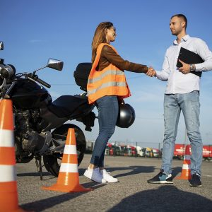 Motorcycle driving school. Instructor and student handshake before start of the classes. Safe ride lessons for motorcycle driving.