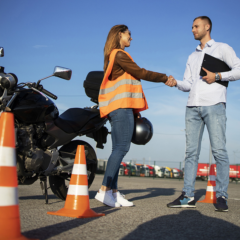 Motorcycle driving school. Instructor and student handshake befo